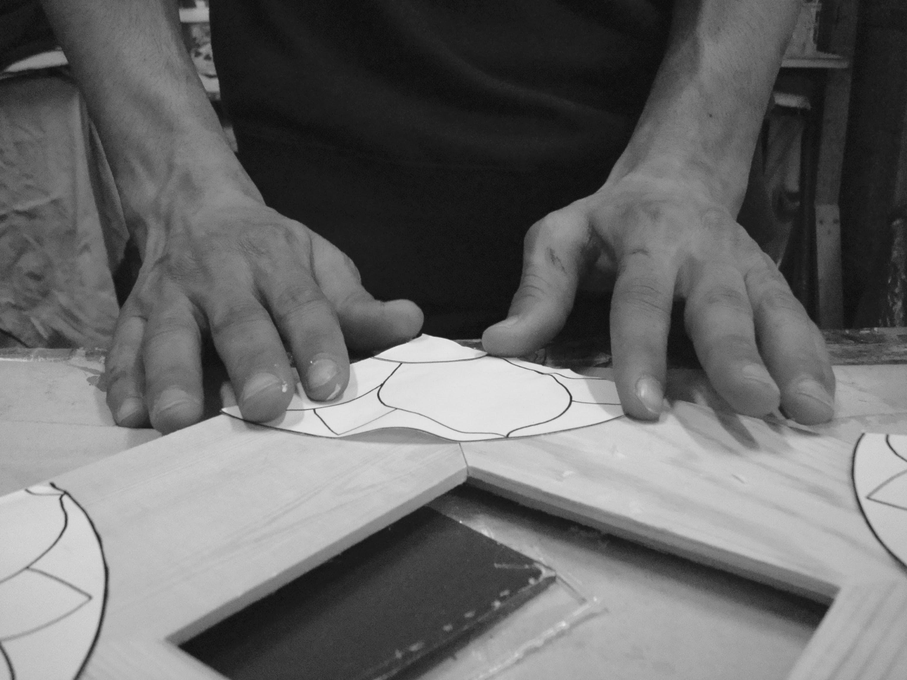 Dettaglio mani di un detenuto che crea una cornice nel laboratorio creativo Arte e Natura del Carcere Minorile di Firenze